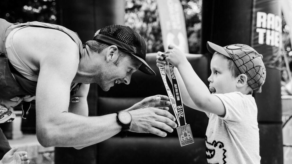 Boy putting medal on dad