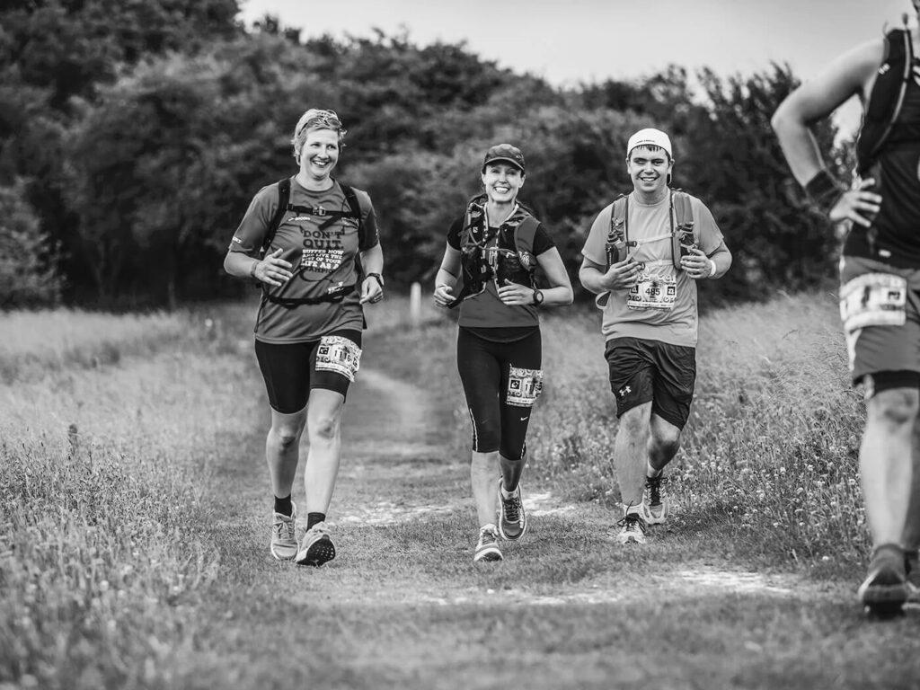 three people running through a field
